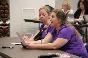 Erika O'Brien, left, looks on as Tara Smith testifies on the need for higher American Sign Language interpreter wages. Both work as interpreters for the district. Compensation lags far behind other employers, including nearby school districts.
